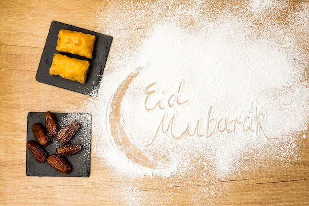 Eid mubarak inscription on flour with eastern sweets
