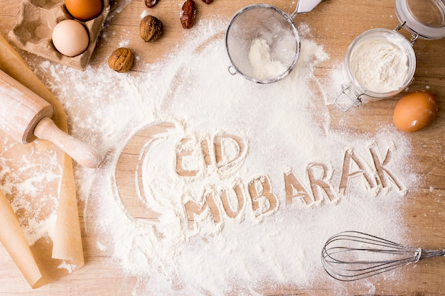 Eid mubarak inscription on flour with rolling pin