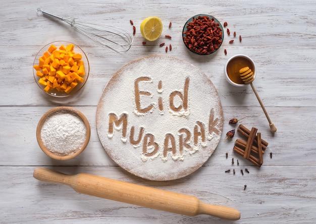 イードムバラク-イスラムの休日のウェルカムフレーズ「ハッピーホリデー」、挨拶は予約済み。アラビア語のベーキング背景。