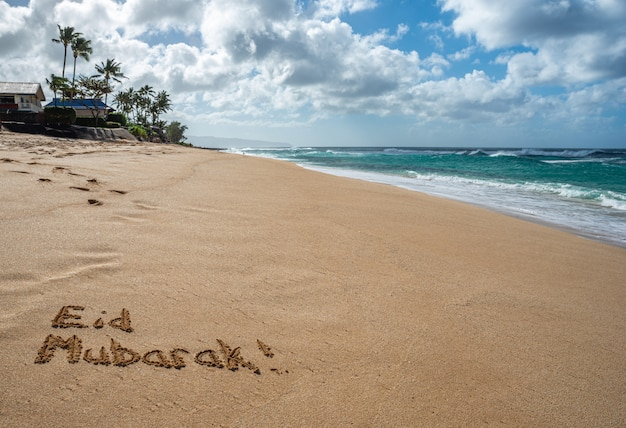 Eid mubarak written in the sand on a beach in hawaii
