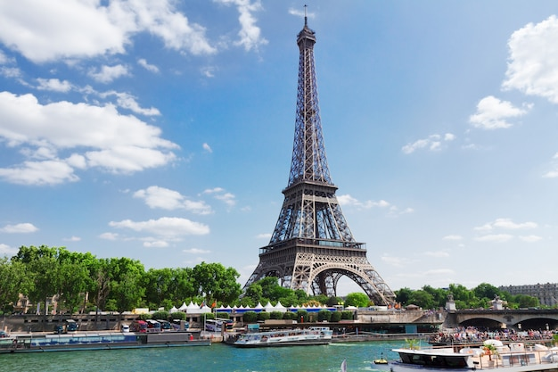 Eiffel tour over seine river waters at summer day, paris,  france
