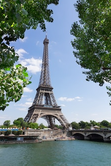 Eiffel tour over seine river with tree green leaves, paris,  france