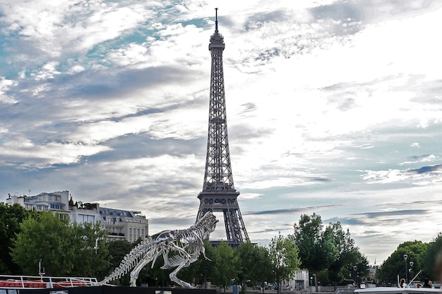 공룡의 금속 설치 동상이 있는 프랑스 파리의 에펠탑
