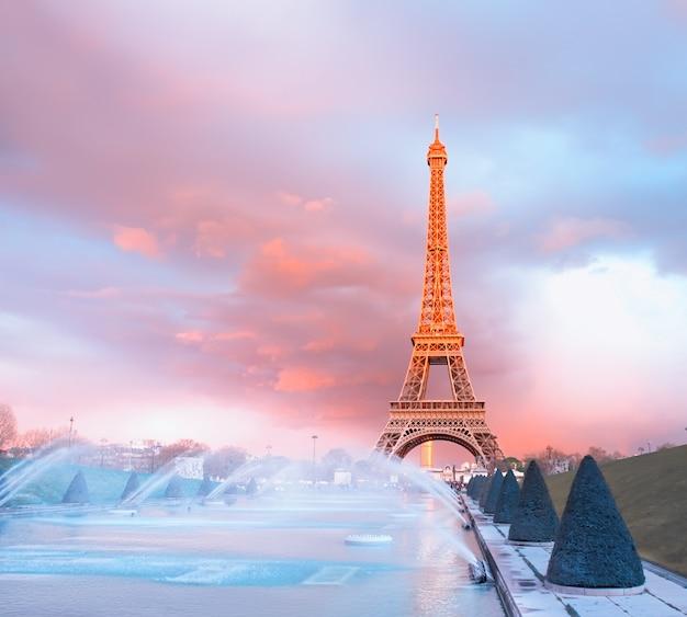 Эйфелева башня на закате наполовину освещена последними лучами заходящего солнца.