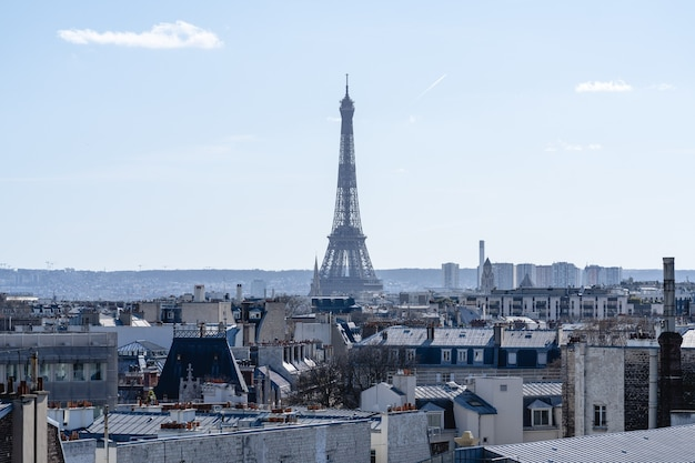 フランスのパリの太陽の下で建物に囲まれたエッフェル塔