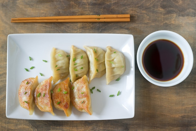 Eight boiled or fried jiaozi or gedza served with soy sauce.
