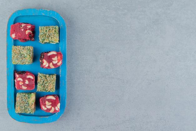 大理石の背景にあるトレイの2つのトルコ菓子の8つの喜び。高品質の写真