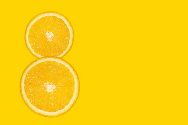 Восьмизначная цифра - нарезанный апельсин, желтый фон, копия пространства. 8 марта женский день яркий фон. свежие сочные фрукты, источник витамина с.