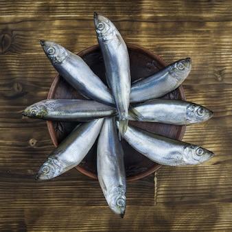 Восемь сельди в глиняной миске на деревянном столе