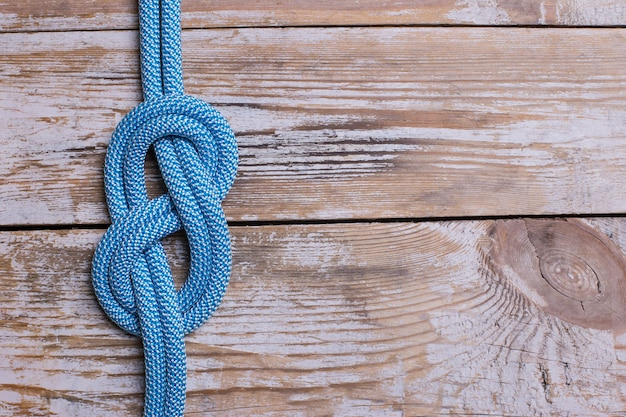 Eight knot on a rope on a wooden background. copy space.