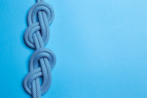 Eight knots on a rope on a blue background. copy space.