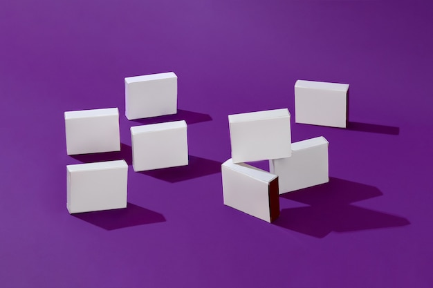 Eight small shadow casting white cardboard boxes