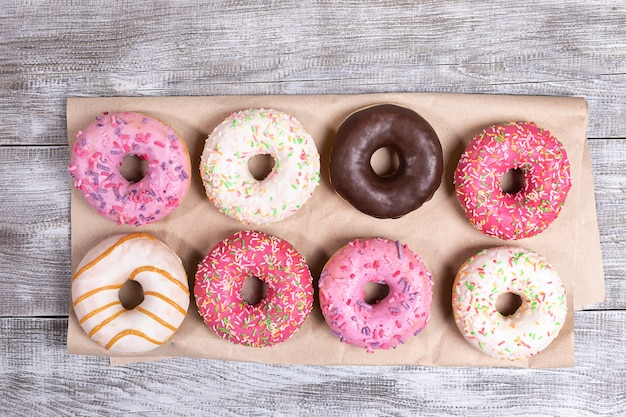 Восемь традиционных пончиков с разноцветной глазурью, аккуратно разложены на упаковочной бумаге на белый окрашенный деревянный стол.