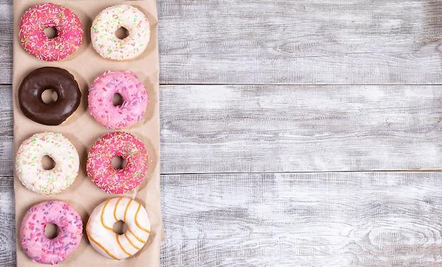 Восемь традиционные пончики с разноцветной глазурью на упаковочной бумаге на белый окрашенный деревянный стол с копией пространства. Premium Фотографии