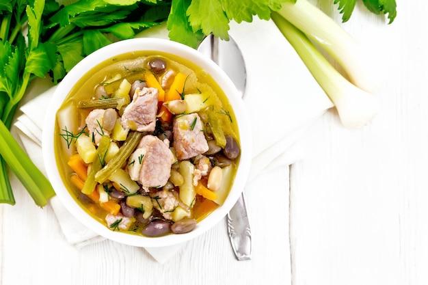 豚肉、セロリ、豆、にんじん、ジャガイモのeintopfスープ、上から木の板の背景にナプキンの白いボウルにネギを入れて
