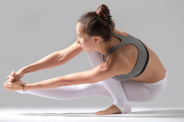 Eka padaをしている女性padangusthasana patch with squat