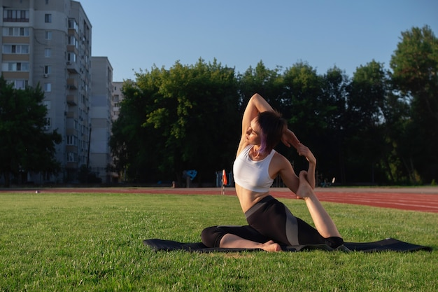 Eka pada rajakapotasana. an athletic, fair-skinned young woman of athletic build is practicing yoga in the park. the concept of healthy living, self-care and wellness
