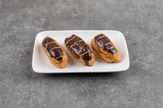 灰色の表面上の白いプレート上のエクラーパスタチョコレートドーナツ。自家製。