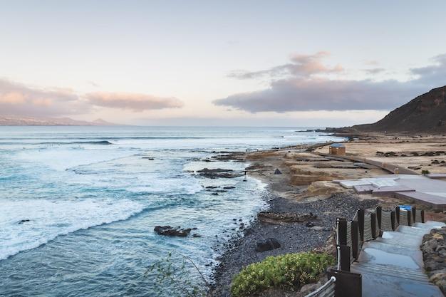 El confital beach at sunrise in gran canaria, canary islands, spain. coast volcanic landscape.