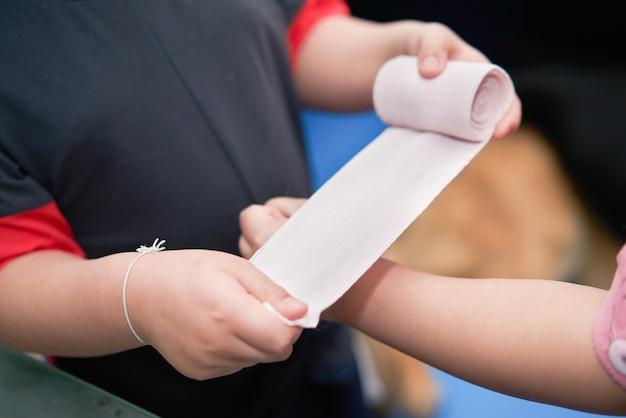 탄성 롤 거즈 붕대는 사고 적용을 위한 응급 처치 압축 관리를 위해 접착제로 손에 잡습니다.