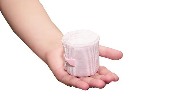 Эластичный рулон марлевой повязки, удерживаемой в руке с клеем для оказания первой помощи, компресс для ухода за несчастным случаем, изолированный на белом