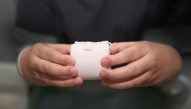 Повязка из эластичной рулонной марли удерживается в руке с помощью клея для оказания первой помощи компресс для ухода при несчастном случае