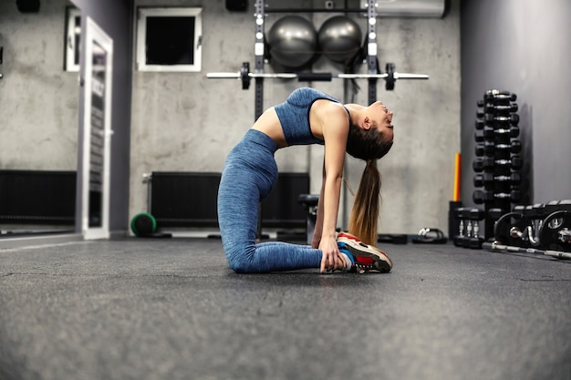 An elastic woman in good physical shape stretches the muscles of the body in the gym