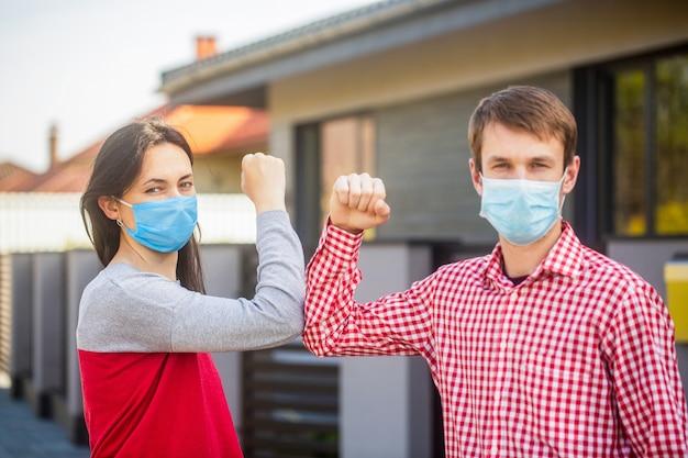 肘の隆起。コロナウイルス、病気、検疫、医療用マスク、covid19。肘でカップルの挨拶。 e