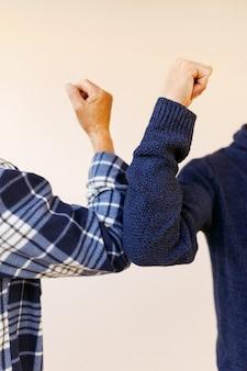 Приветствие ударом локтя во избежание распространения коронавируса. двое друзей-друзей здороваются, толкая их локтями, вместо того, чтобы приветствовать их объятиями или рукопожатием. не пожимайте руки.