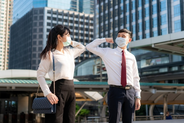 Elbow bump is new novel greeting to avoid the spread of coronavirus two asian business friends meet in front of office building.