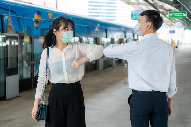 Elbow bump is new novel greeting to avoid the spread of coronavirus two asian business friends meet in subway station.