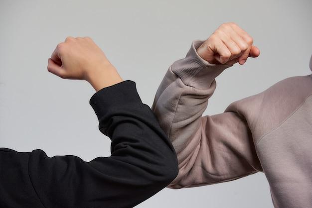 肘のバンピング。抱擁や握手で挨拶する代わりに、スウェットシャツを着た男の子と女の子が肘をぶつける