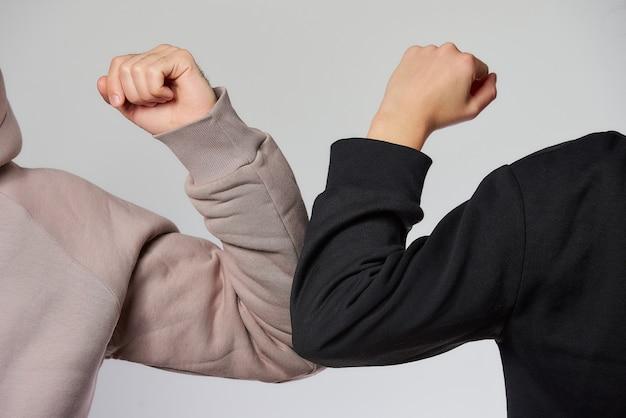 肘のバンピング。コロナウイルス(covid-19)の蔓延を避けるための挨拶の新しい方法。スウェットシャツを着た男性と女性は、抱擁や握手で挨拶する代わりに、肘をぶつけます。