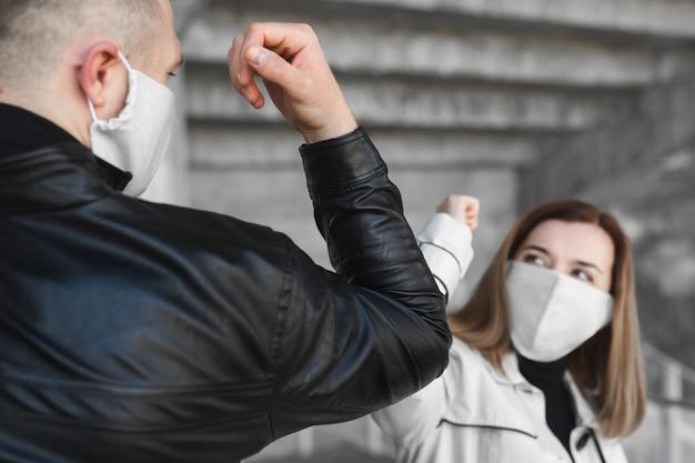 肘のバンピング。コロナウイルスの蔓延を回避する新しい挨拶方法covid19。男と女が抱擁や握手ではなく肘をぶつける