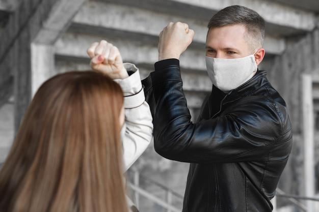 Локоть натыкаясь. новый способ приветствия, позволяющий избежать распространения коронавируса covid19. мужчина и женщина бьют локтями вместо объятий или рукопожатия