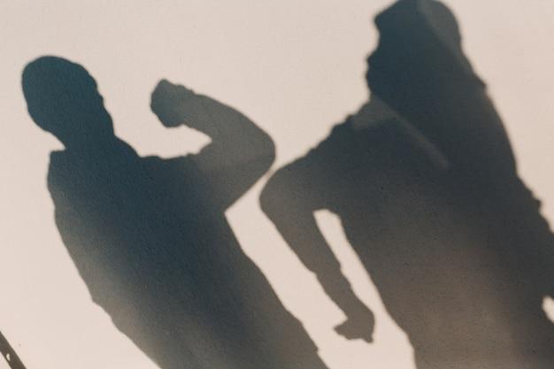 코로나바이러스 covid-19 판데미아의 벽에 그림자 두 사람의 팔꿈치 충돌 안전 인사말. 뉴 노멀.