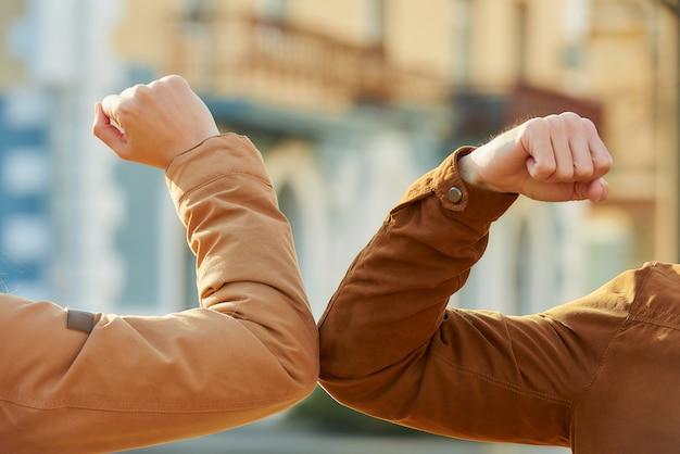 コロナウイルス(covid-19)の蔓延を避けるための肘の挨拶。男と女が素手で路上で出会う。ハグや握手で挨拶する代わりに、肘をぶつけます。