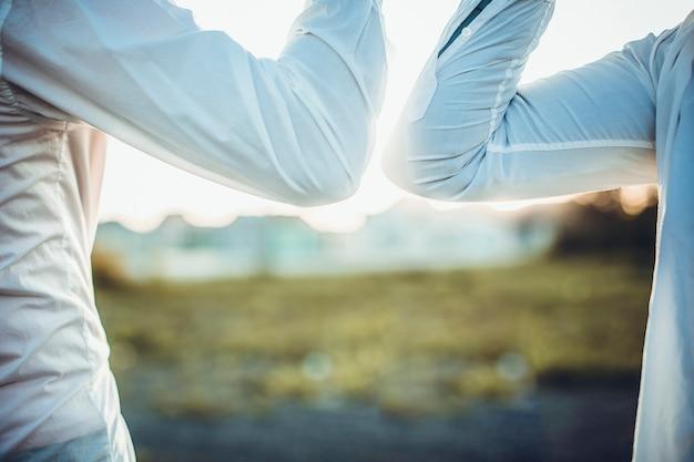 コロナウイルスcovid-19の蔓延を避けるための肘の挨拶。ビジネスマンは日没で素手で会います。ハグや握手で挨拶する代わりに、肘をぶつけます。
