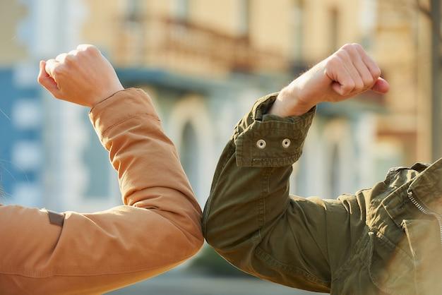 コロナウイルス(covid-19)の蔓延を避けるための肘の挨拶。同僚は通りで素手で集まります。ハグや握手で挨拶する代わりに、肘をぶつけます。