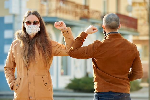 コロナウイルス(covid-19)の蔓延を避けるための肘の挨拶。医療用マスクをした男性と女性が素手で路上で出会います。ハグや握手で挨拶する代わりに、肘をぶつけます。