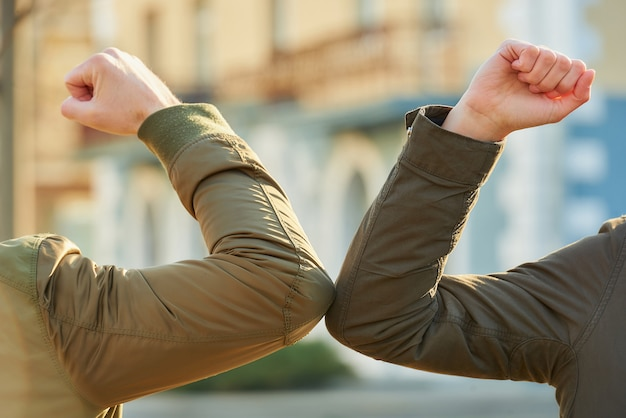 コロナウイルス(covid-19)の蔓延を避けるための肘の挨拶。男と女が素手で路上で出会う。ハグや握手で挨拶する代わりに、肘をぶつけます。クローズアップ写真。