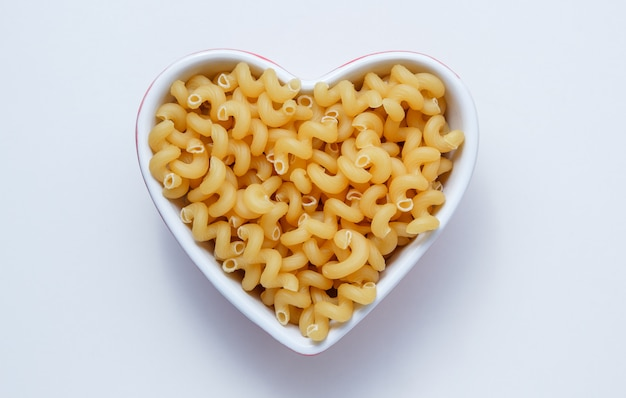 Elbow macaroni pasta in a heart shaped bowl top view on a white table