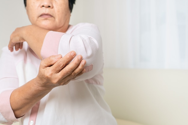 Elbow pain old woman suffering from elbow pain at home, healthcare problem of senior concept