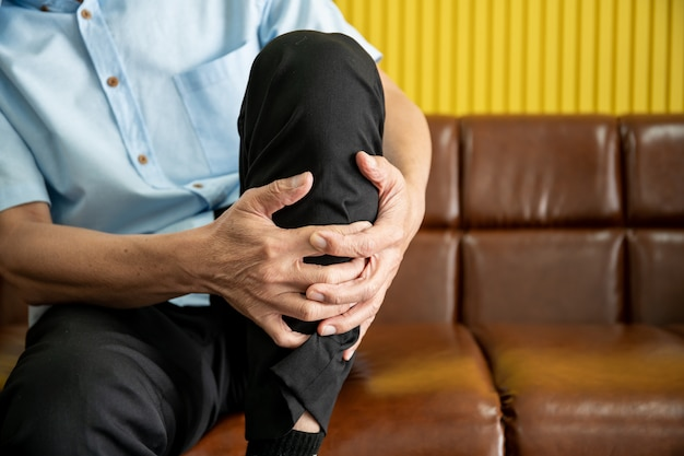 Elder asian man sitting on safa hurt his leg and touching leg painfully.