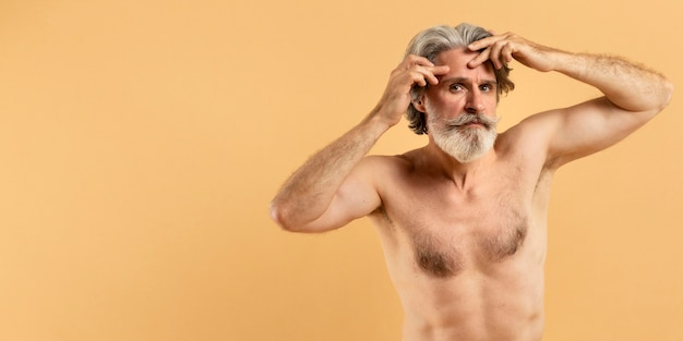 Elder bearded man pointing out wrinkles with copy space