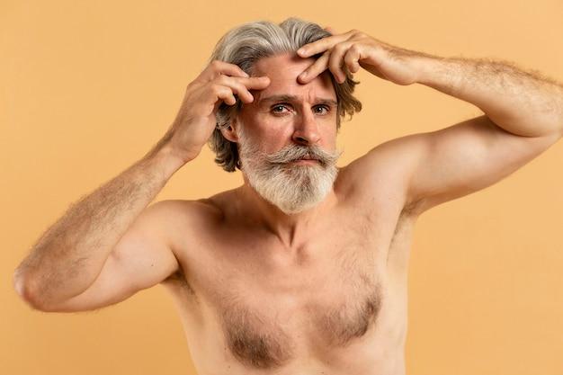 Elder bearded man pointing out wrinkles