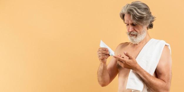 Elder bearded man using cream with copy space