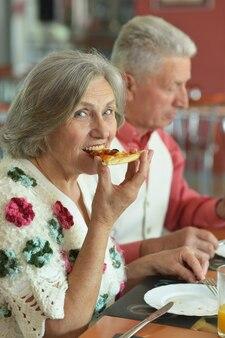 カフェでピザを食べる老夫婦