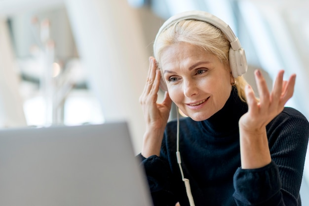 Elder business woman having a video call on laptop with headphones