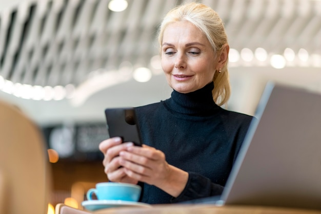 Старшая деловая женщина, работающая на смартфоне и ноутбуке